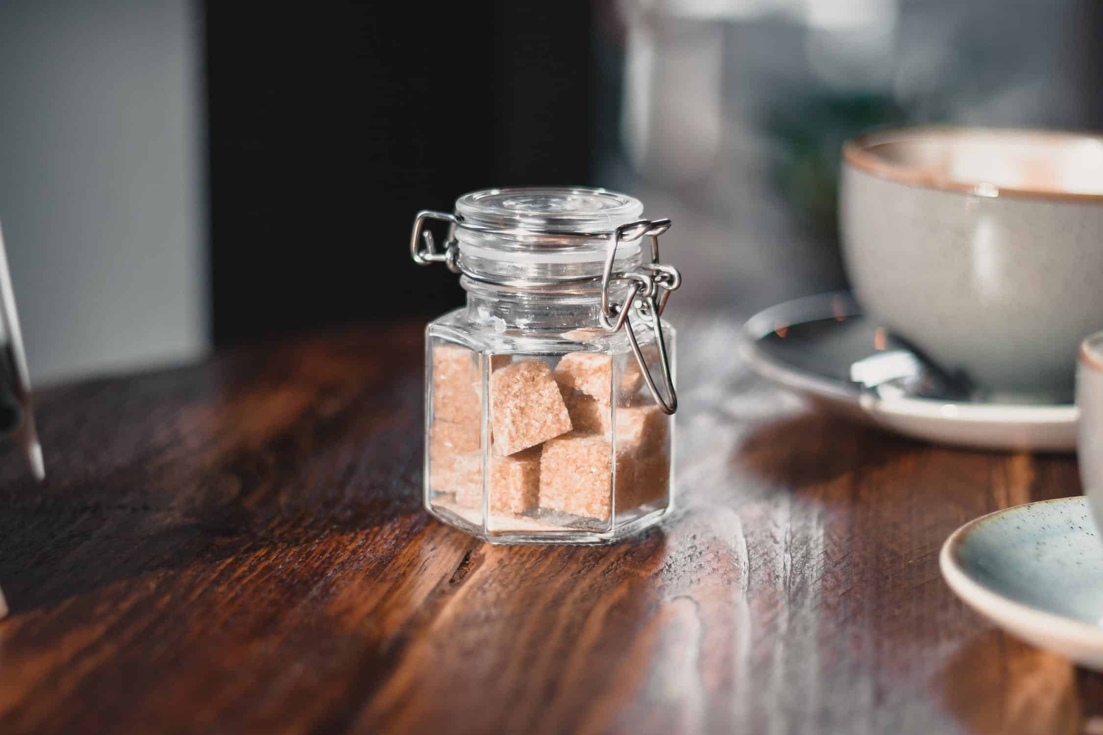 Brown sugar cubs in a small kilner jar on a table