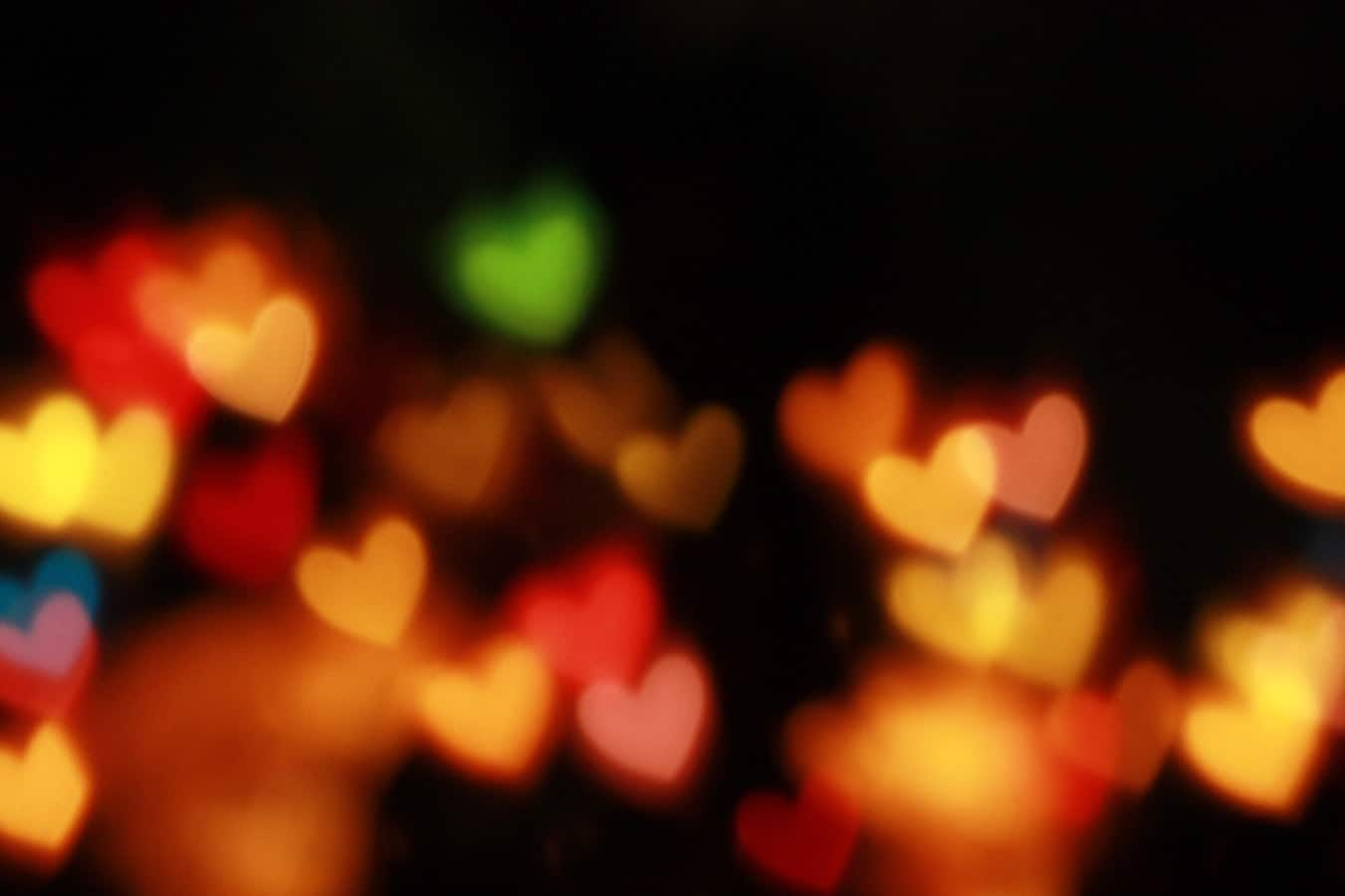 Love heart shaped lights glowing amber in the dark