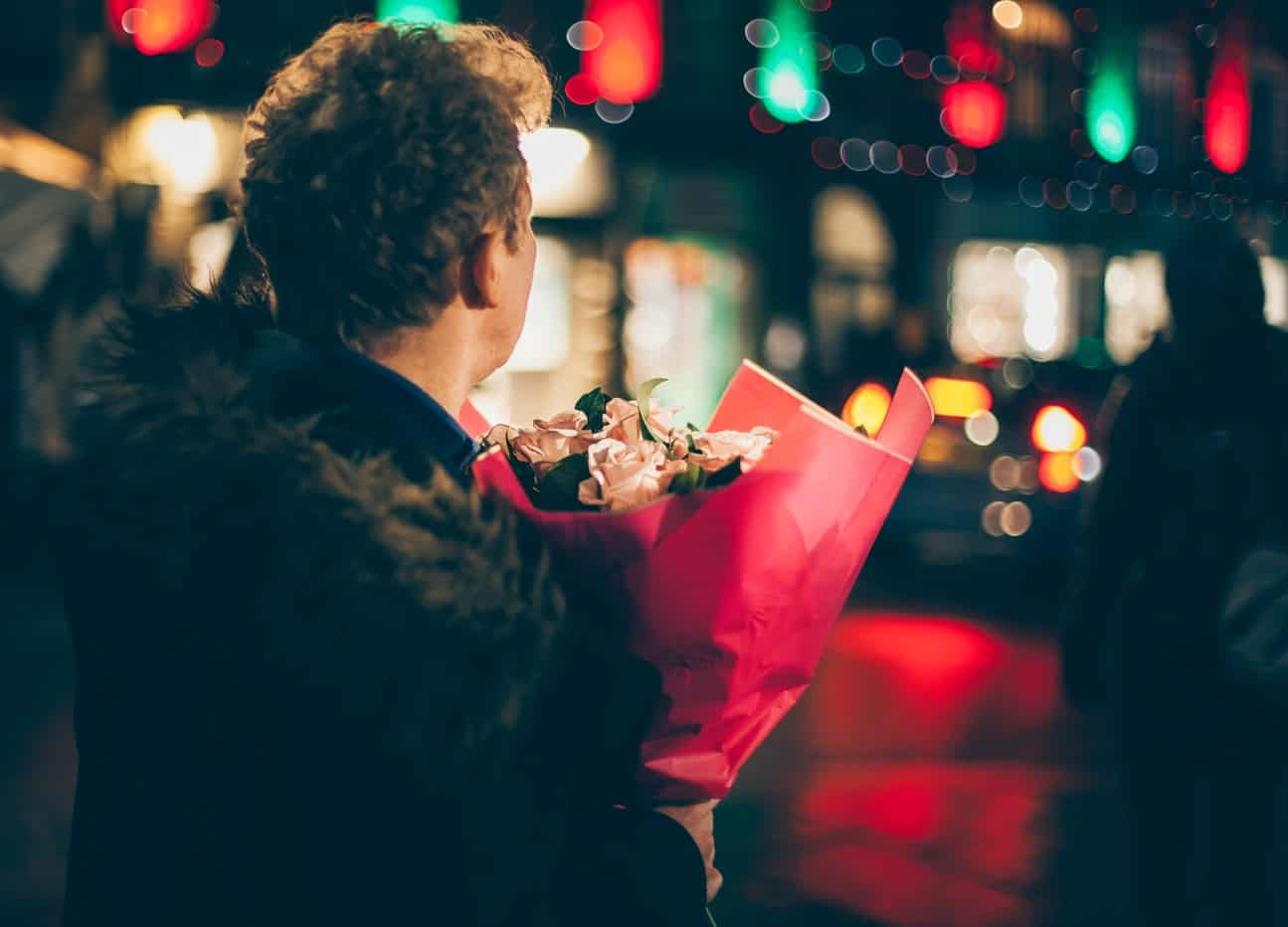 A man stood outside at night with a bouquet of flowers
