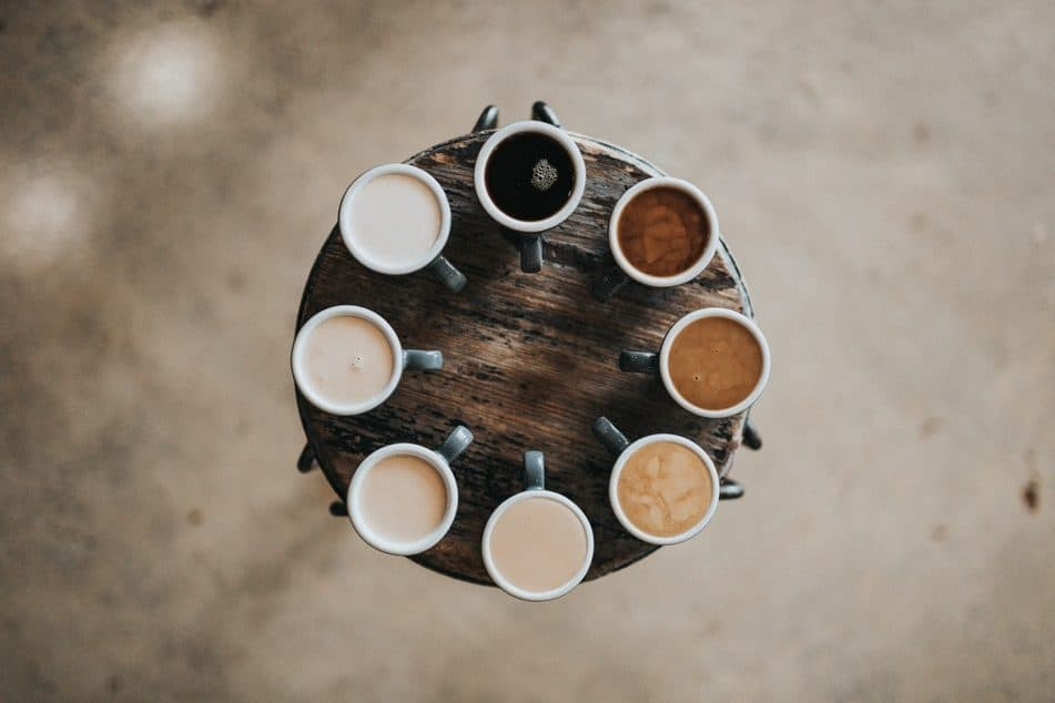 A birds-eye shot of different strengths of coffees around a circular wooden tray