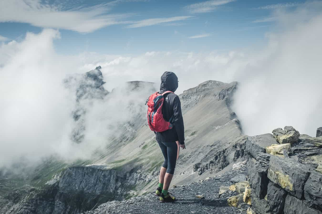 A woman wearing an anorak standing on high up in the clouds