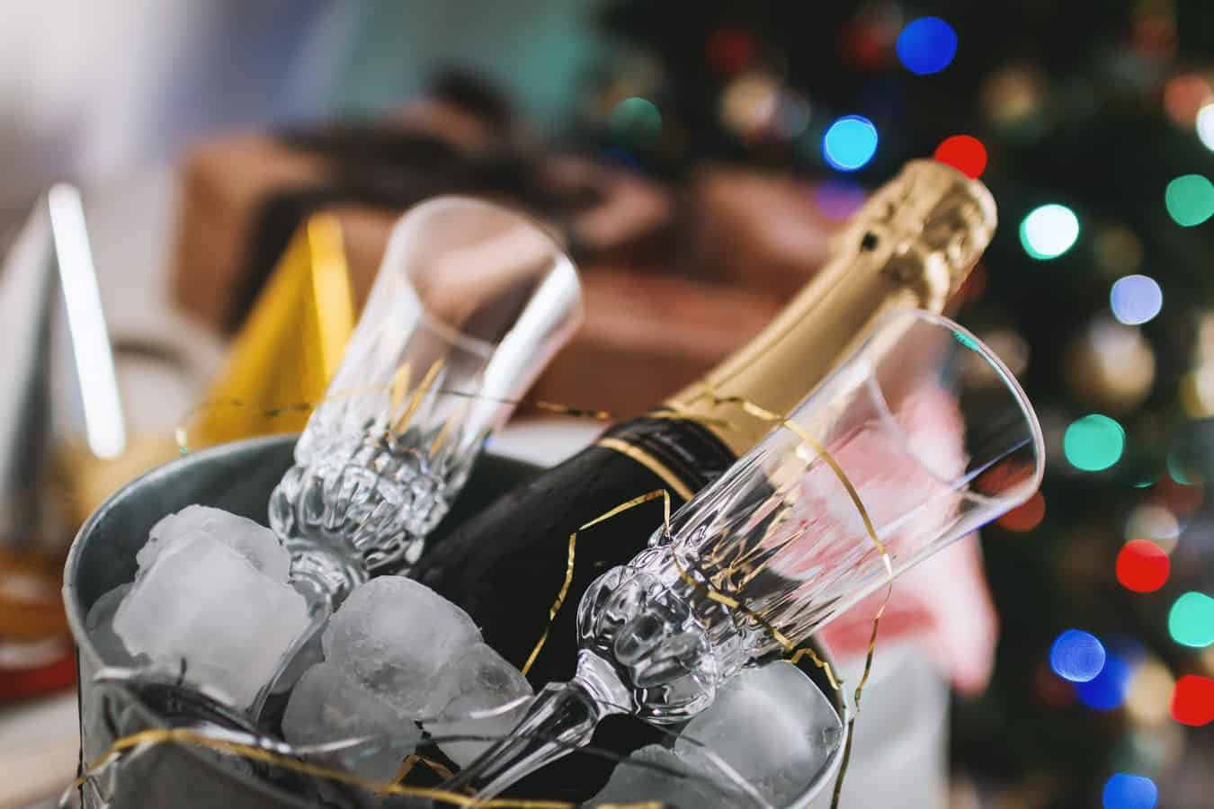 A bottle of champagne in a metal bucket with ice and glasses