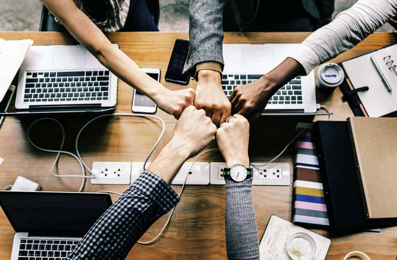 5 people fist bumping over a work space