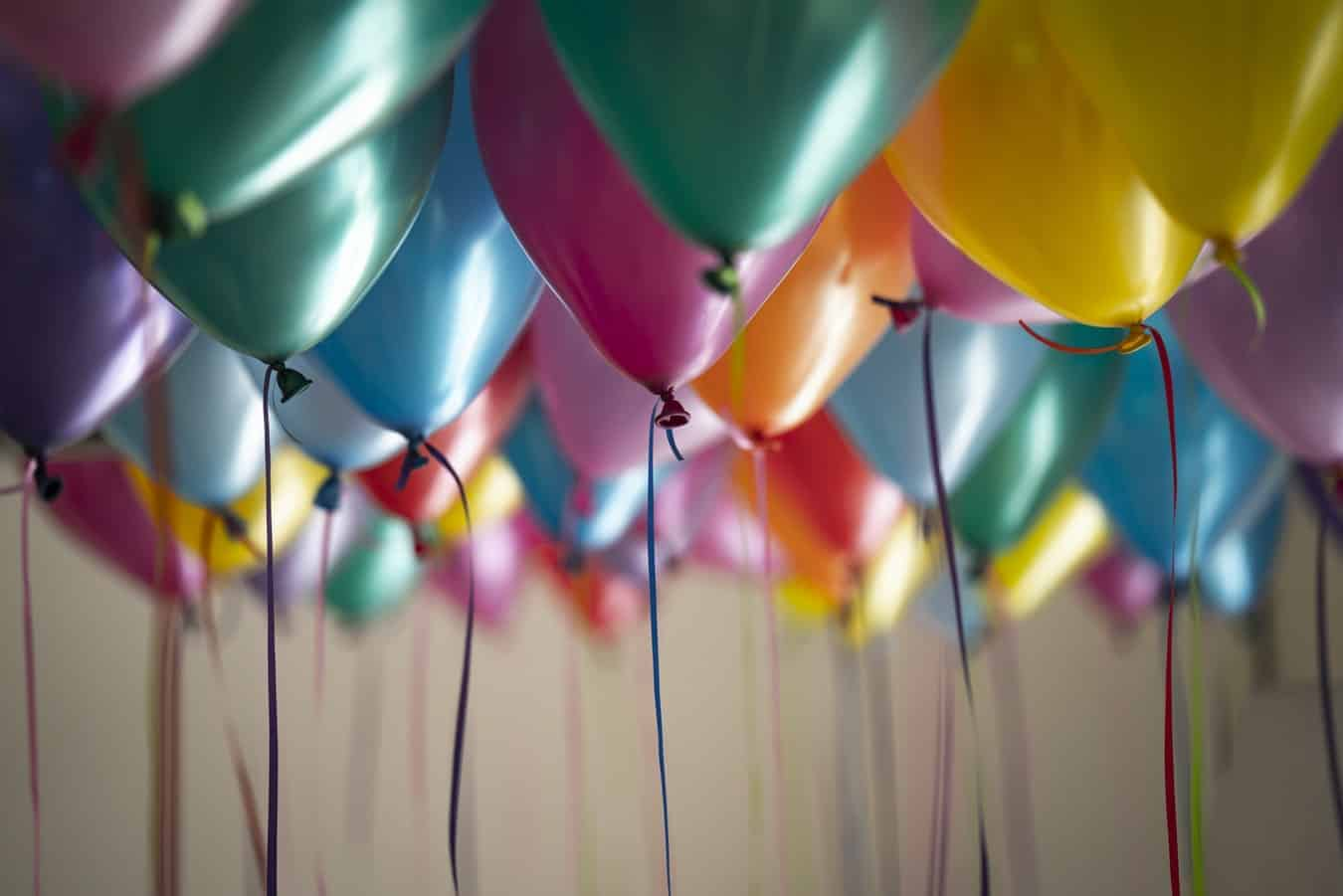 A range of different coloured helium balloon on the ceiling