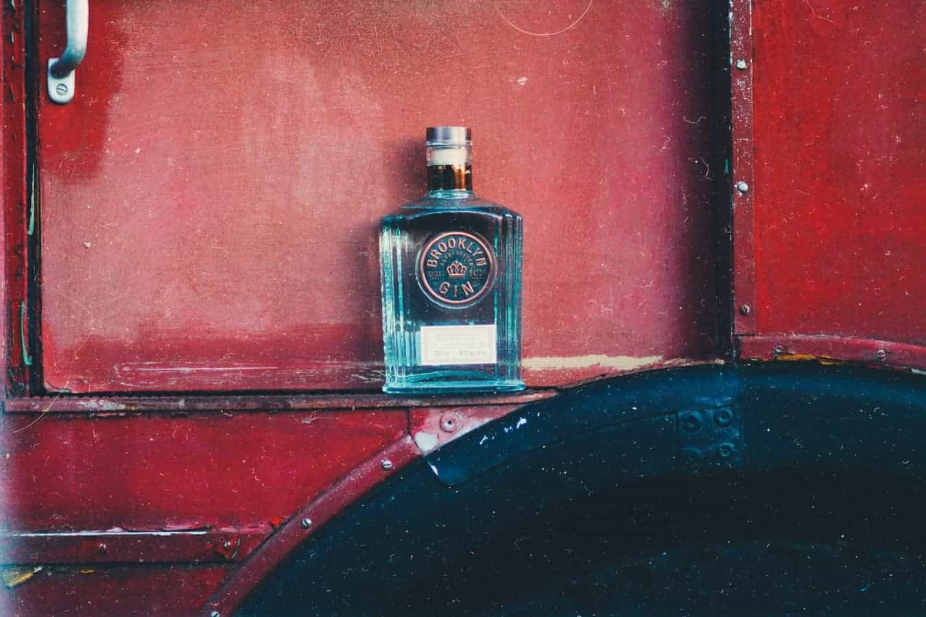 A square blue glass bottle of gin against a red wall