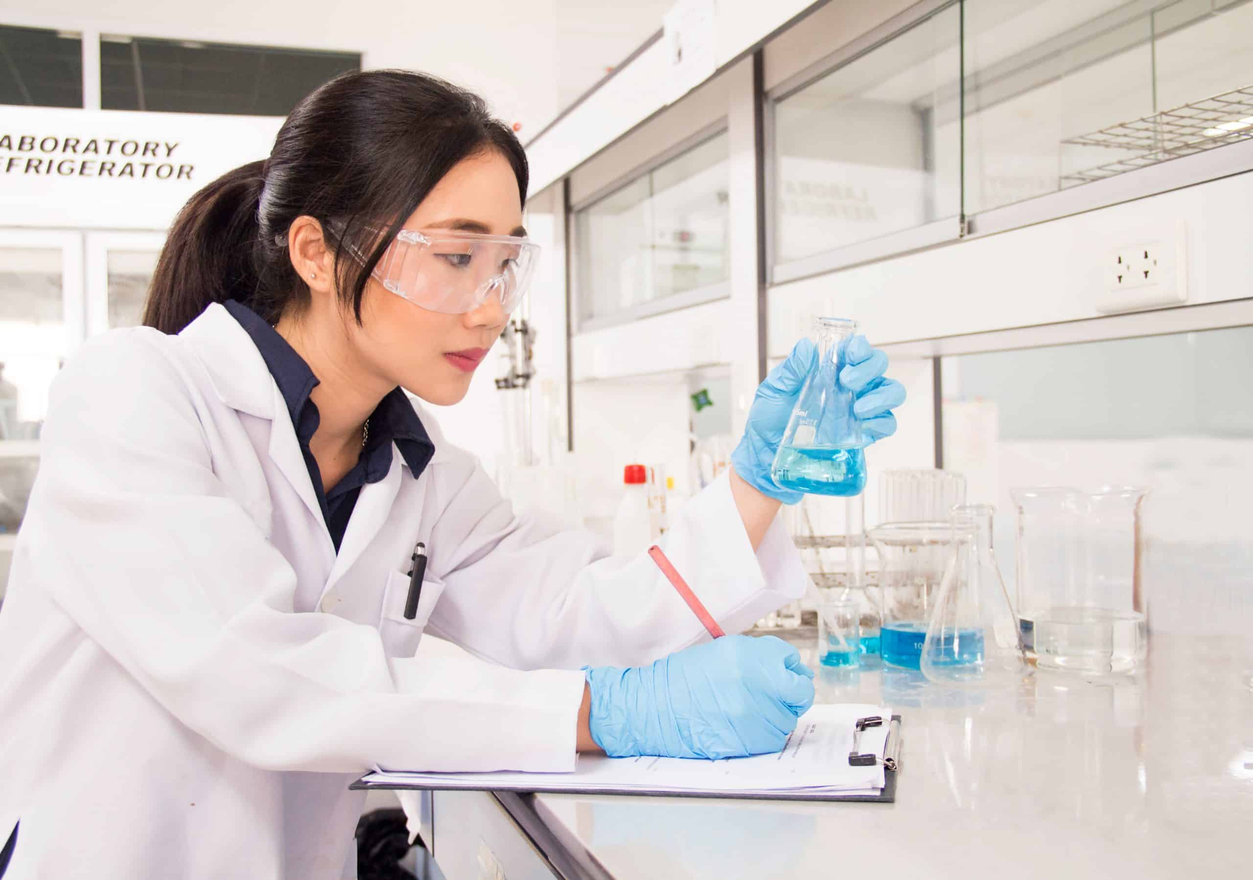 Woman analysing chemicals in a lab