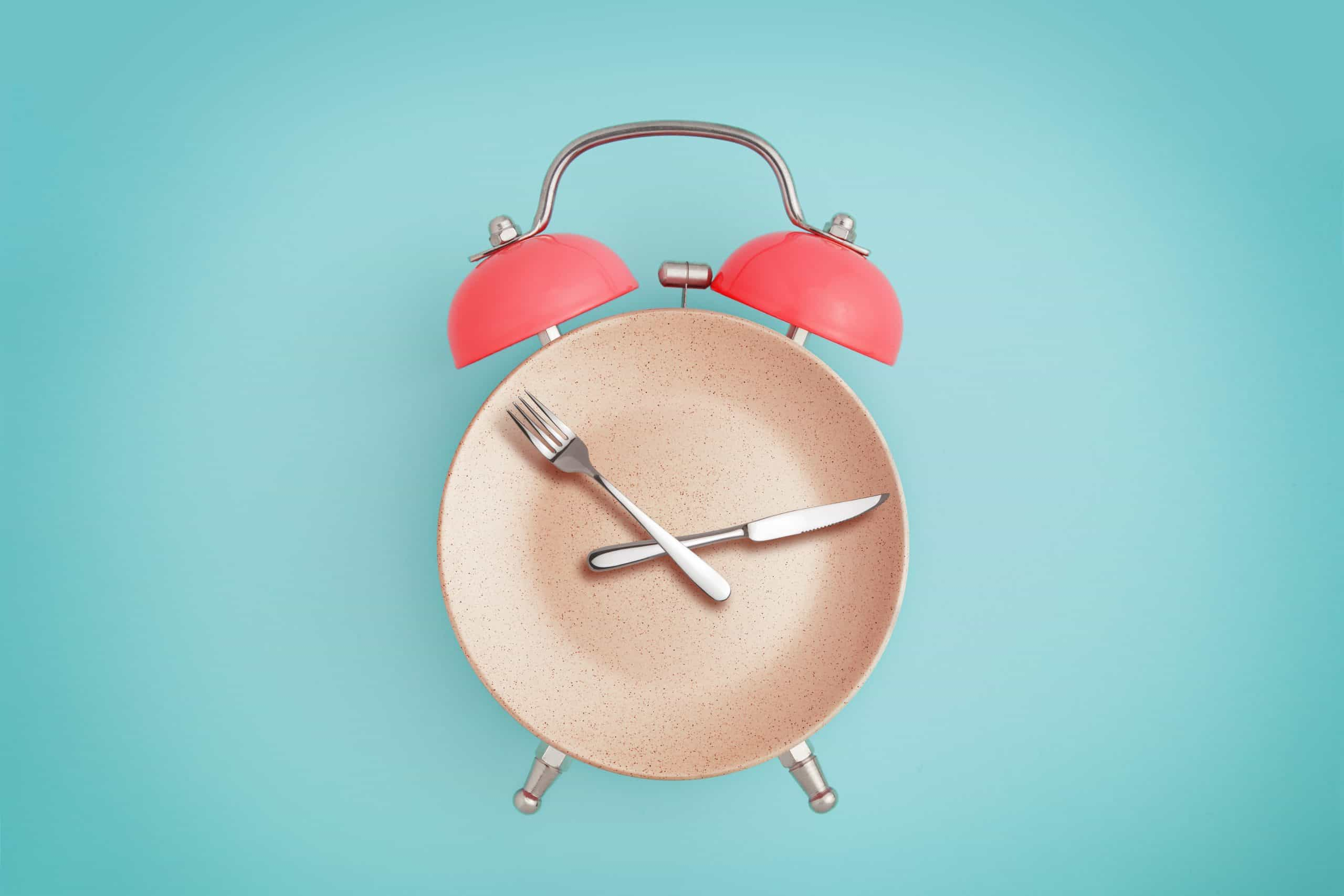 Alarm clock and plate with cutlery . Concept of intermittent fasting