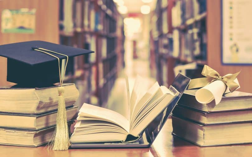 Graduation cap on stack of books in library