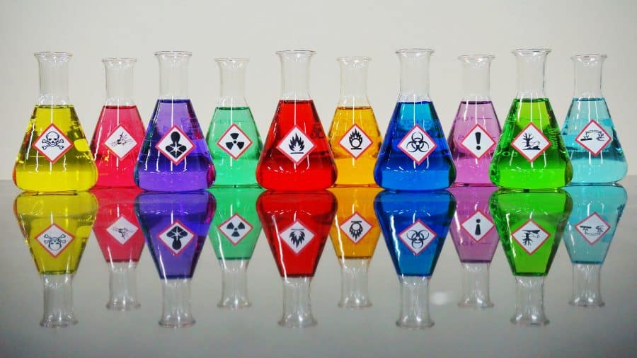 Many of colorful chemicals on Erlenmeyer flask with Variety type of chemical hazard warning symbols labels on