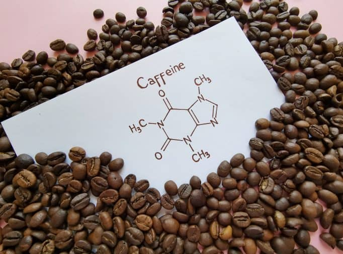 Structural chemical formula of caffeine molecule with roasted coffee beans
