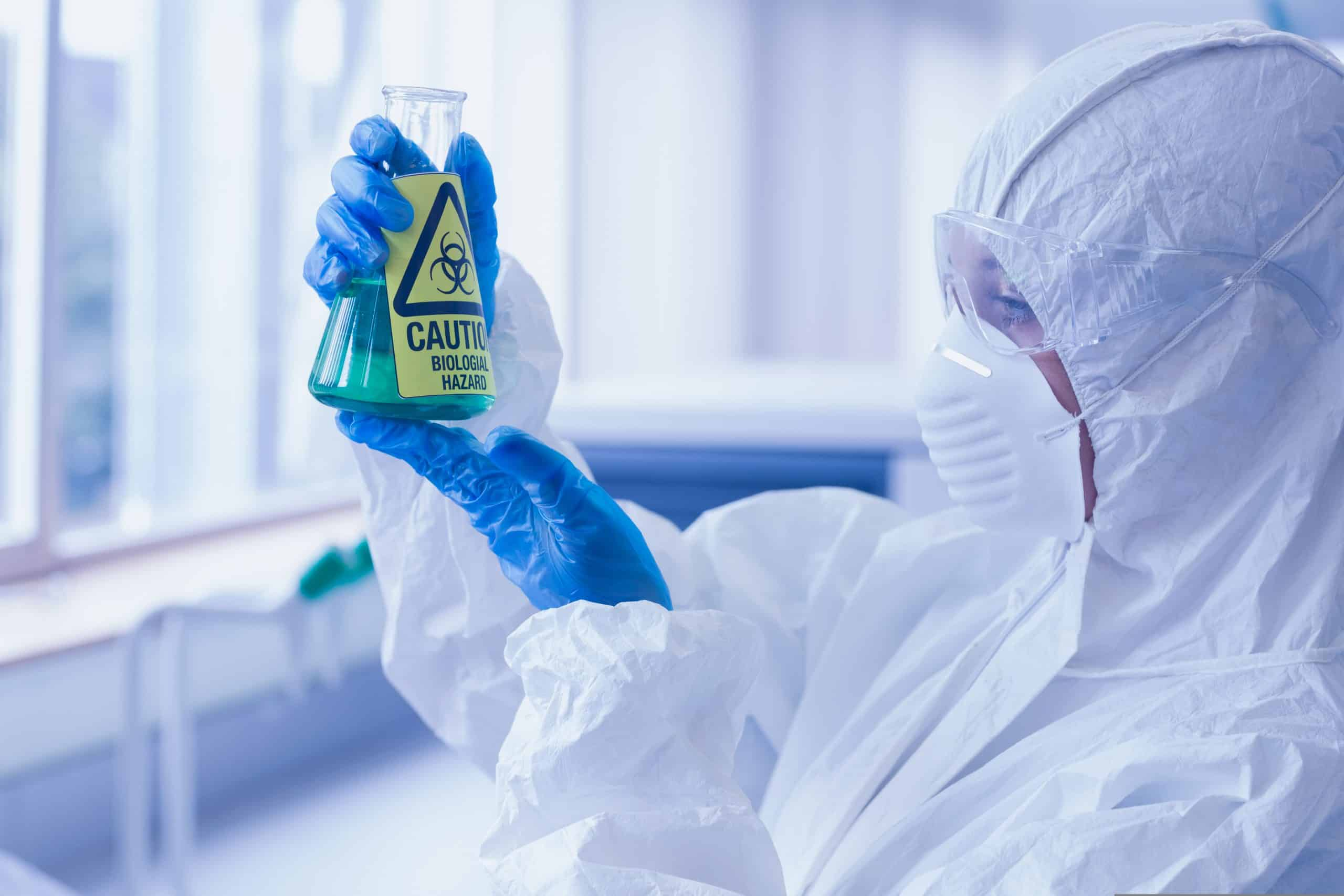 Close-up side view of a scientist in protective suit looking at hazardous blue chemical