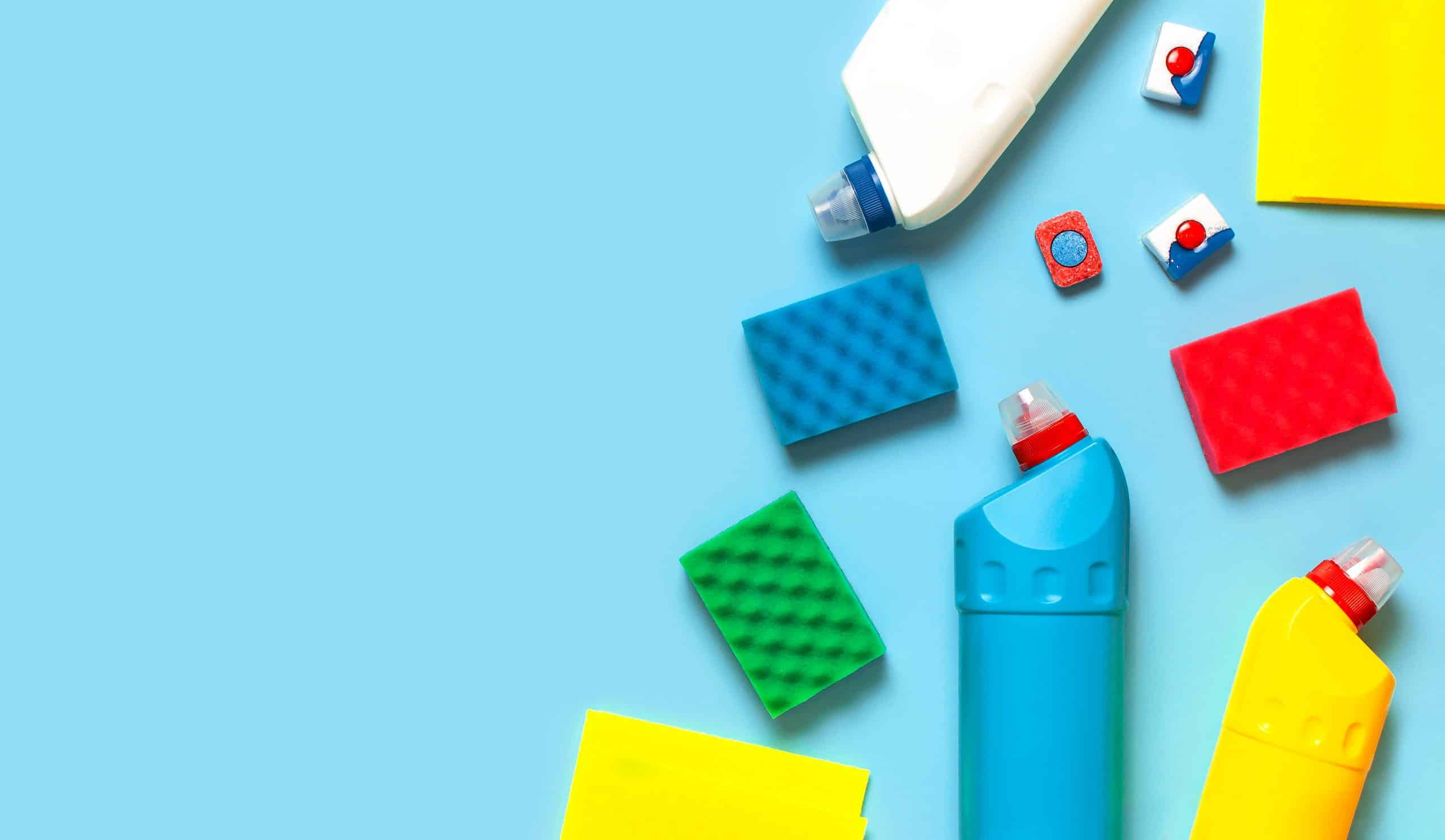 Household chemicals, disinfectant, bleach, antibacterial gel, yellow rubber gloves, sponge, rags, dishwasher tablets on blue background.