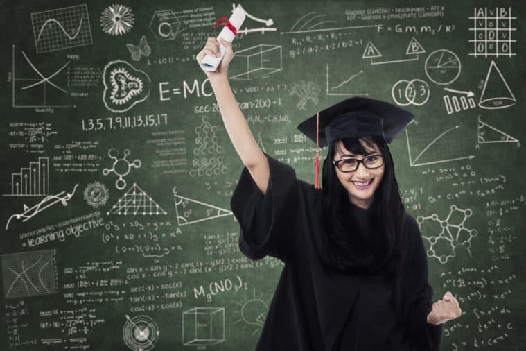 Woman in graduation gown holding degree in front of chemistry blackboard
