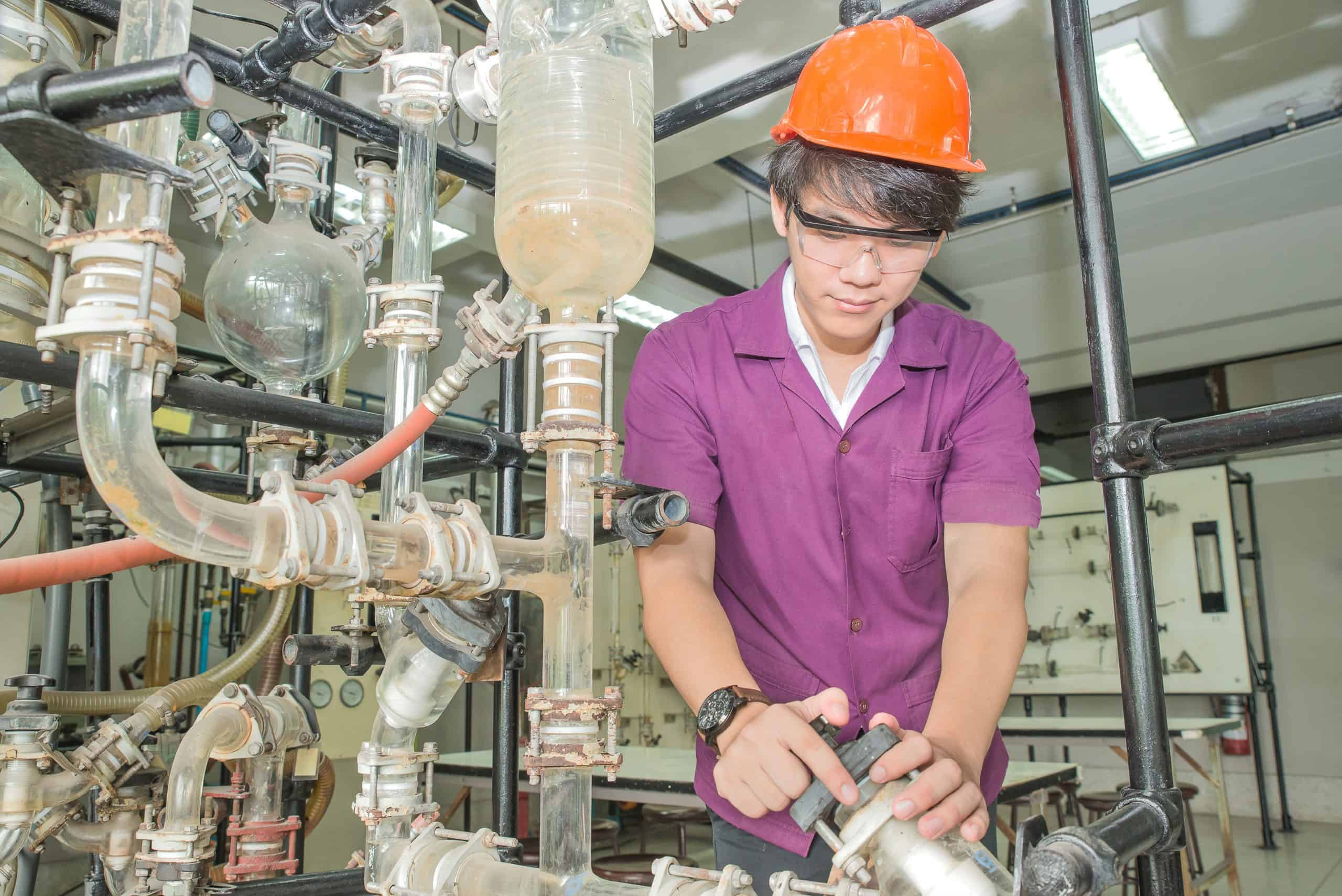 Chemical engineer student turning pipeline pump for training in laboratory