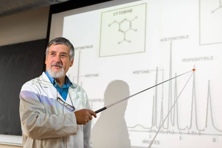 Senior chemistry professor in a lectuee pointing to a screen