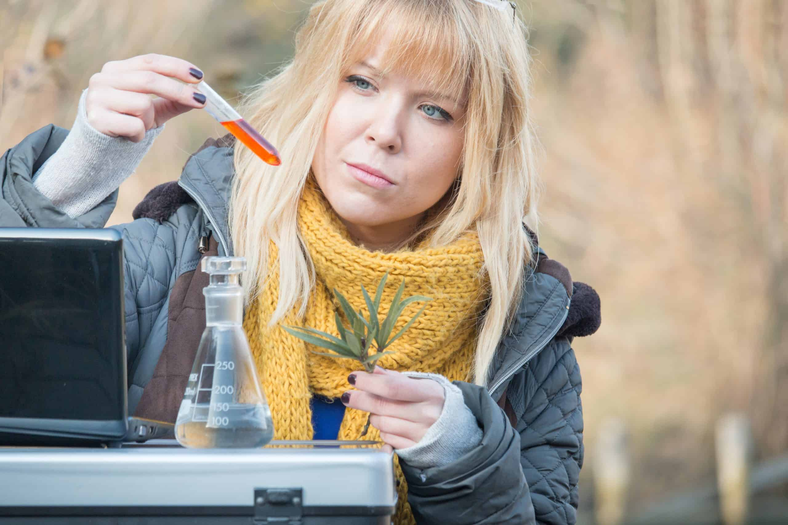 young environmental scientist at field doing biological research outdoors with colorful chemical liquid in test tube