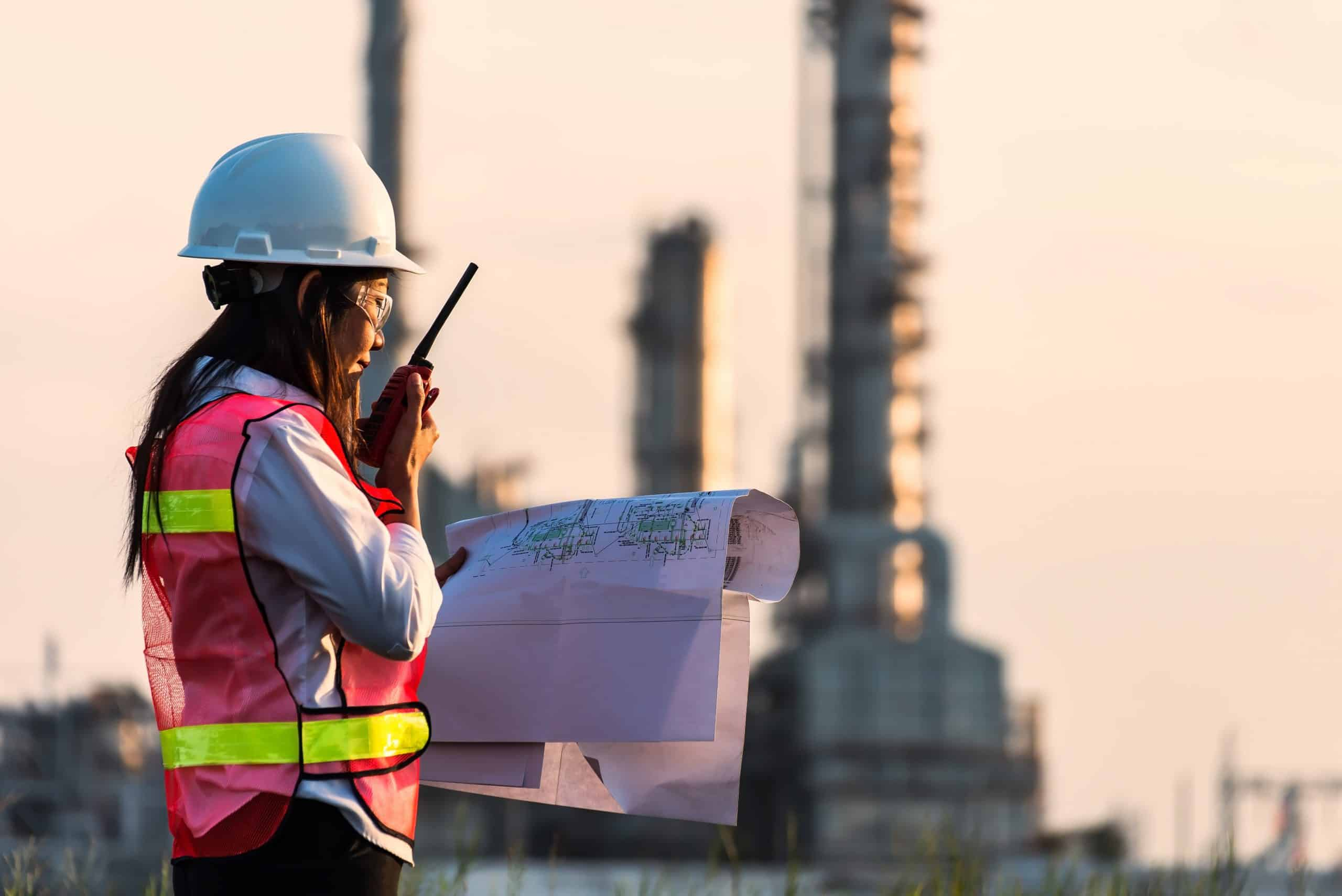 Chemical engineer with safety helmet in front of Oil refinery